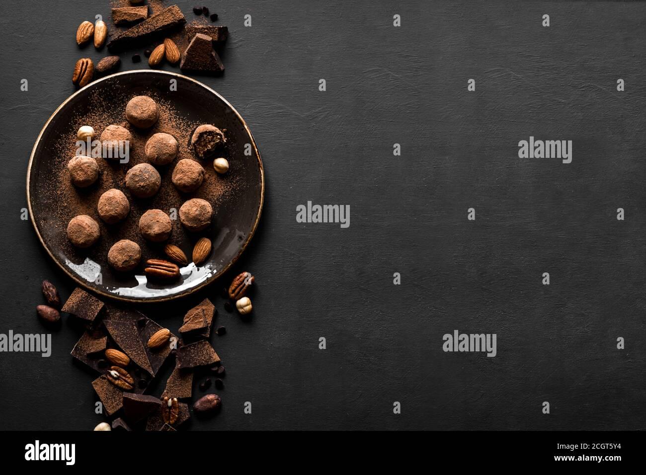 Trufas de chocolate con chocolate negro y nueces sobre fondo negro, vista superior, espacio de copia. Bolas de energía de chocolate caseras veganas o trufas para desse Foto de stock