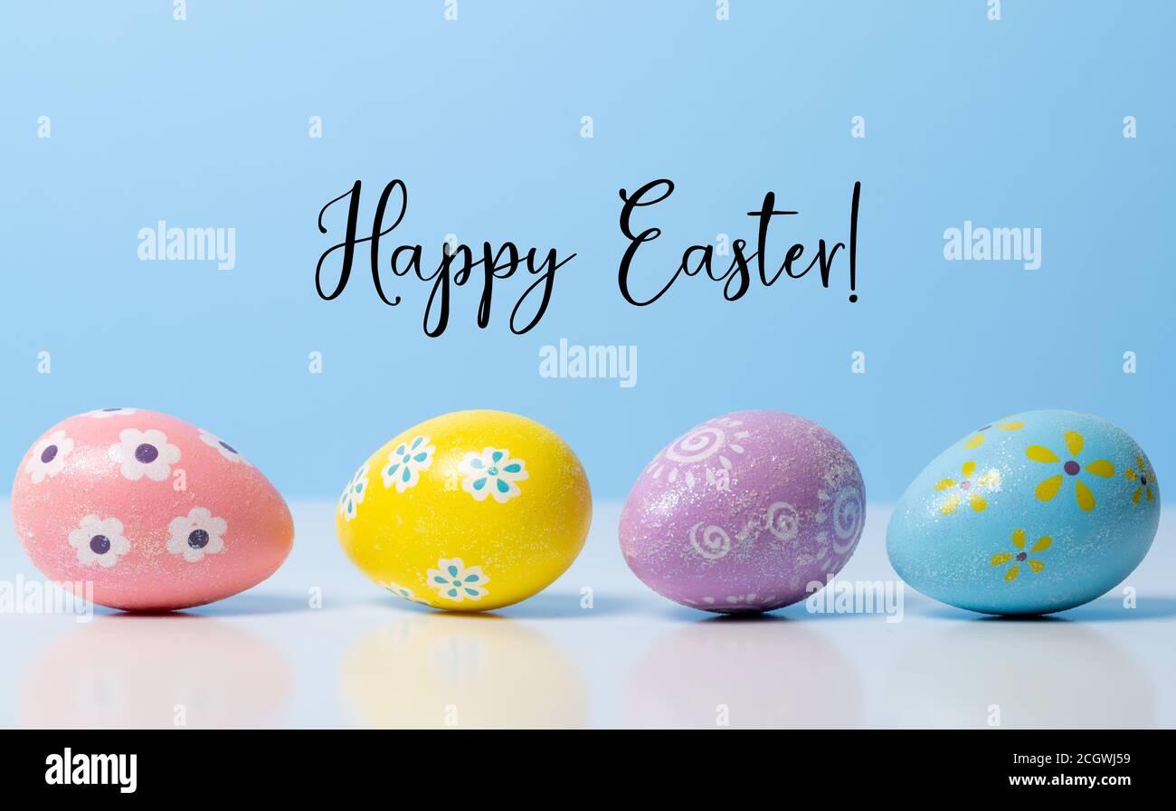 Coloridos huevos de Pascua sobre fondo azul con saludo Foto de stock