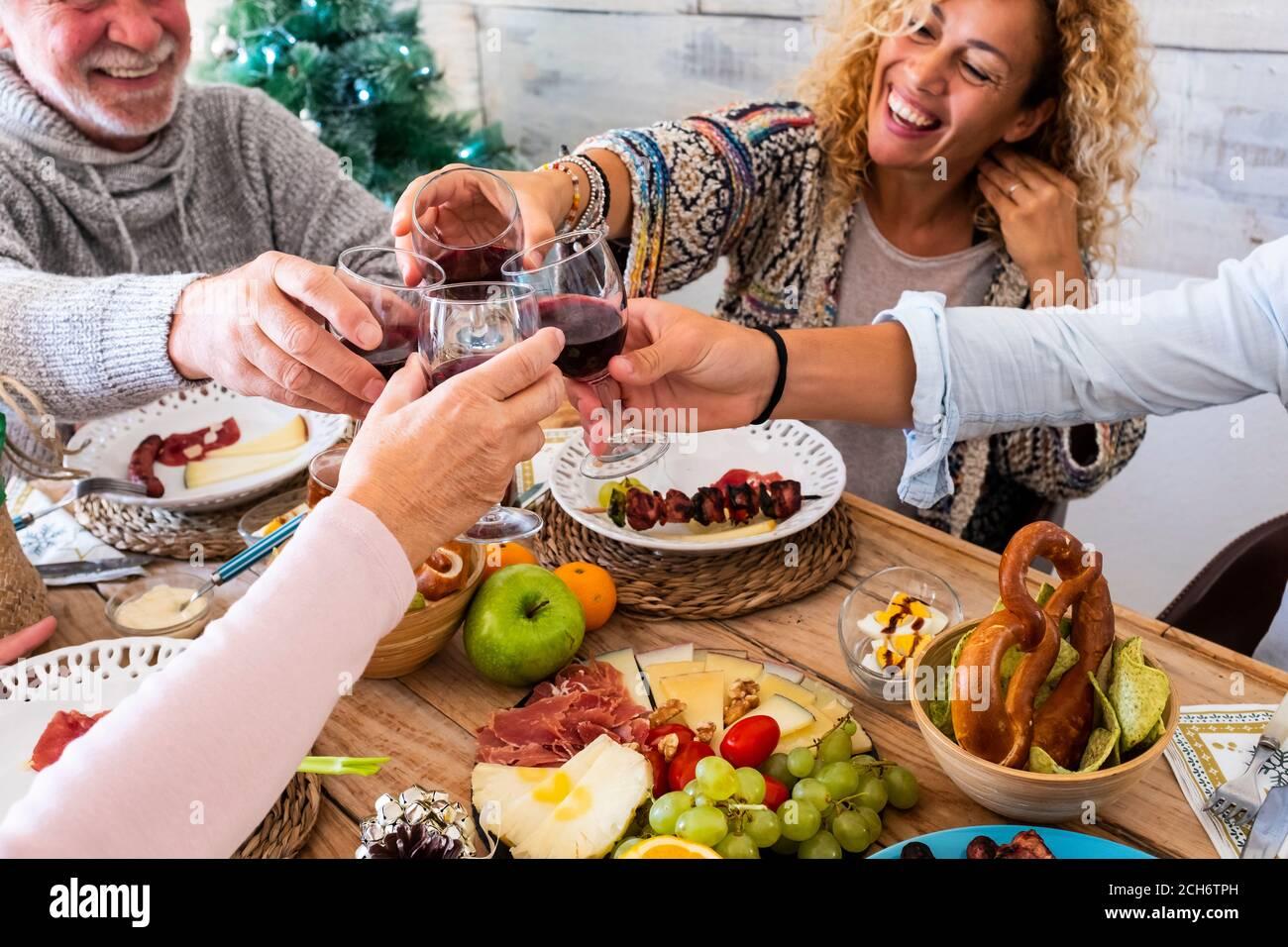 Los amigos de la familia se divierten juntos en el invierno comiendo la comida encendido una mesa de madera - concepto de amistad y gente caucásica disfrutar de la celebración en casa o. Foto de stock
