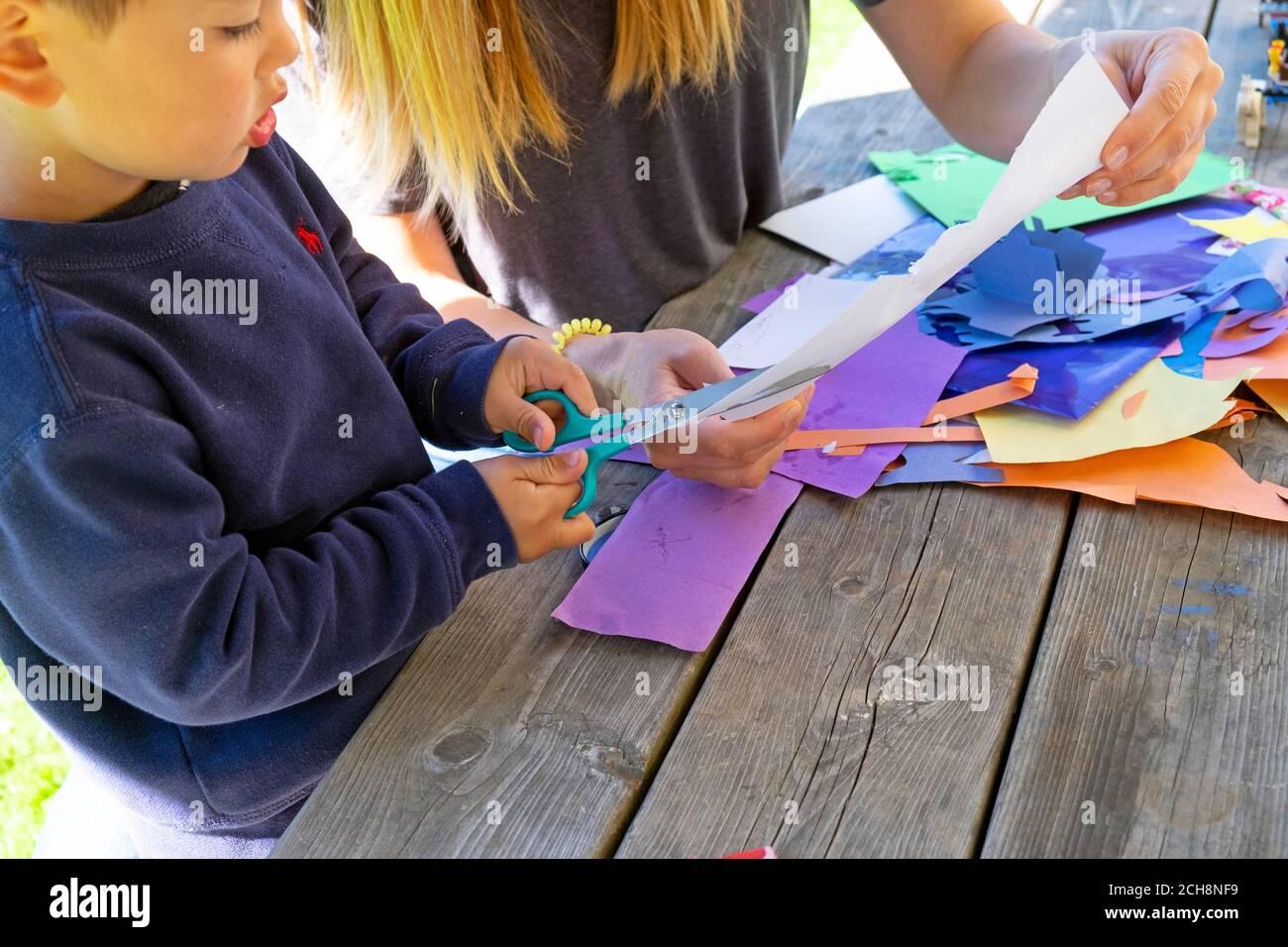 Niño pequeño de 3 años aprendiendo a cortar papel con tijeras sentarse fuera en una mesa con papel de arte de colores Carmarthenshire Wales Reino Unido KATHY DEWITT Foto de stock