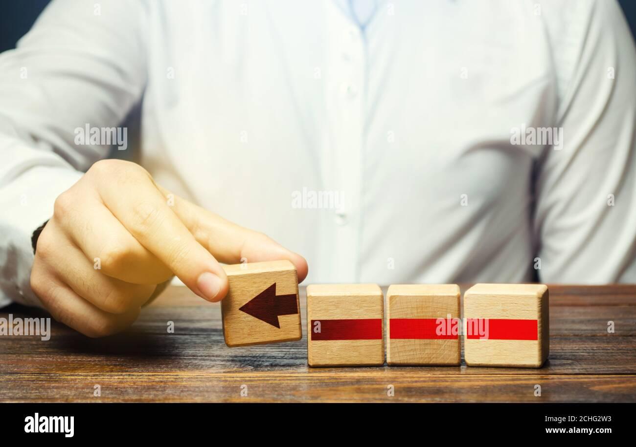El hombre construye una flecha roja a partir de bloques. Desarrollo empresarial, concepto de proceso de crecimiento. Progreso y avance. Promoción de carrera, mejora de habilidades. Foto de stock