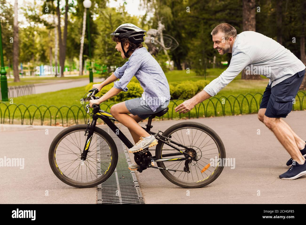 Hijo aprendiendo a montar en bicicleta con su padre feliz Foto de stock