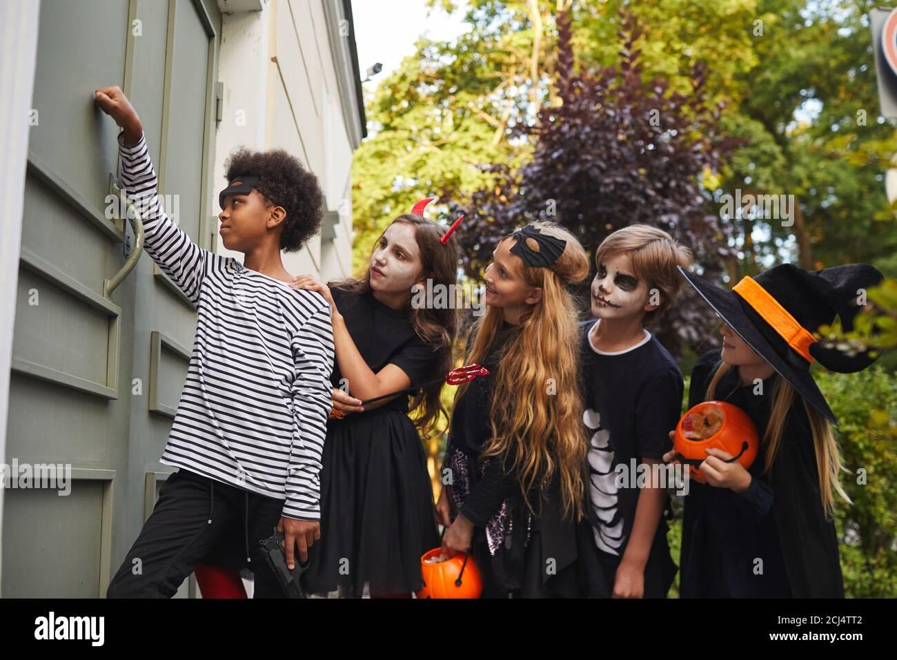 Vista lateral de un grupo multiétnico de niños que visten trajes de Halloween llamando al timbre de la puerta mientras tratan o tratan juntos, copiar espacio Foto de stock