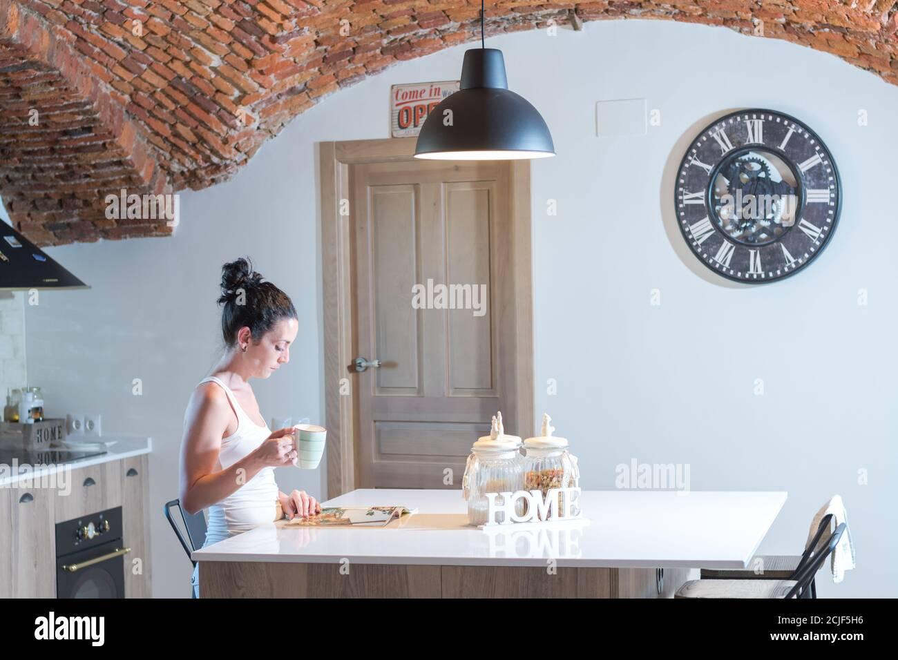 joven chica morena leyendo una revista mientras bebía café la cocina Foto de stock