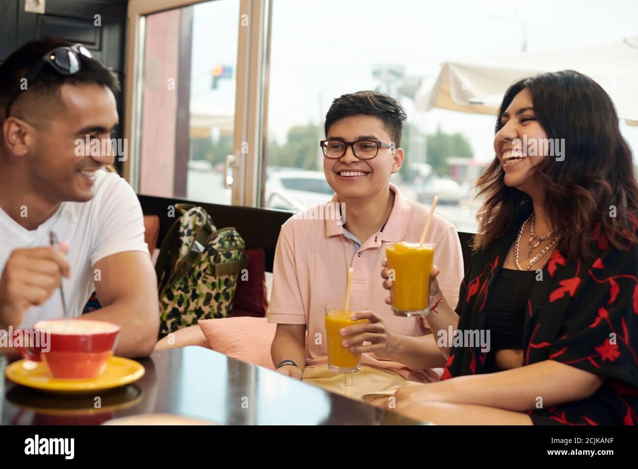 Reunión de amigos. Tres amigos multiétnicos están discutiendo algo y se ríen de ello. Foto de stock