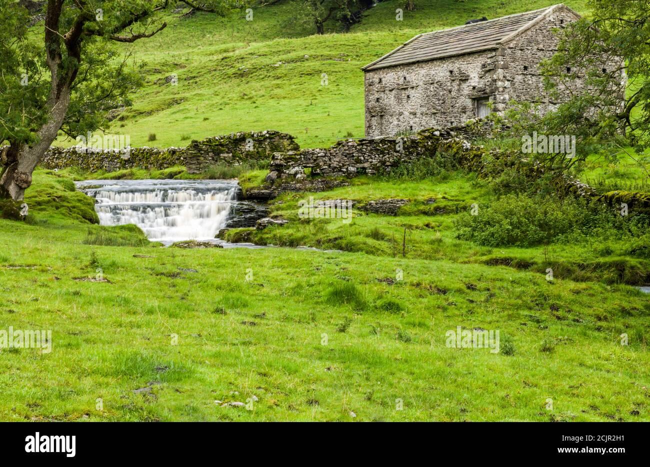 Cascada y el granero Dales en Cray, un pequeño puesto avanzado en la carretera de Upper Wharfedale a Bishopdale en el Parque Nacional de Yorkshire Dales. Foto de stock