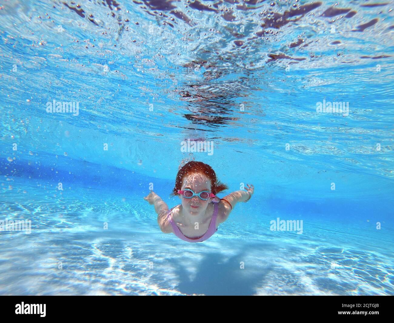 Joven Red cabeza niña nadar bajo el agua con gafas en un Piscina Foto de stock