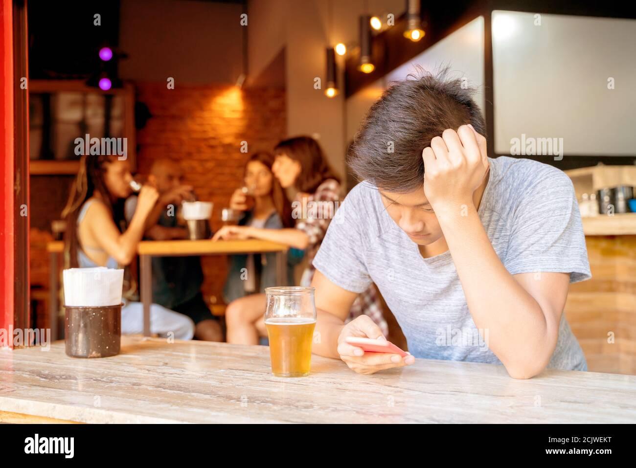 Un triste guapo excluyó a un chico asiático sentado solo en un bar usando su smartphone Foto de stock