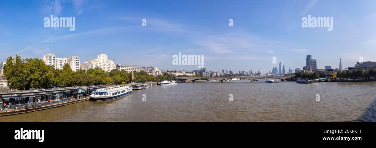 Vista panorámica hacia el este a lo largo del río Támesis desde Embankment Pier hasta Shell-Mex House, Waterloo Bridge y rascacielos de la ciudad de Londres Foto de stock