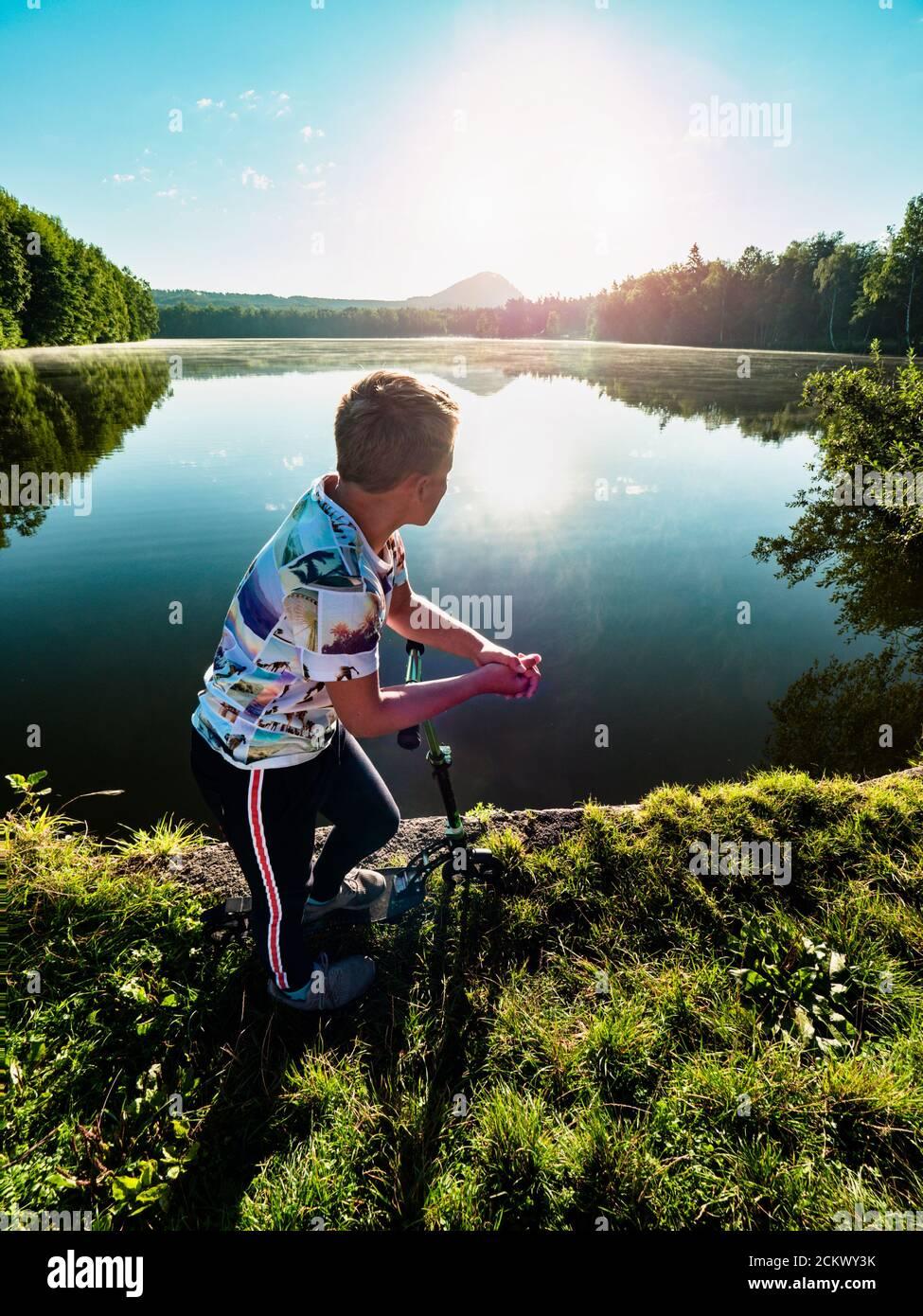 Rubio de pelo chico con scooter se encuentra en un camino de parque a lo largo del lago. Concepto de deportes infantiles. El sol de la noche está haciendo llamaradas y reflexiones en el agua. Foto de stock