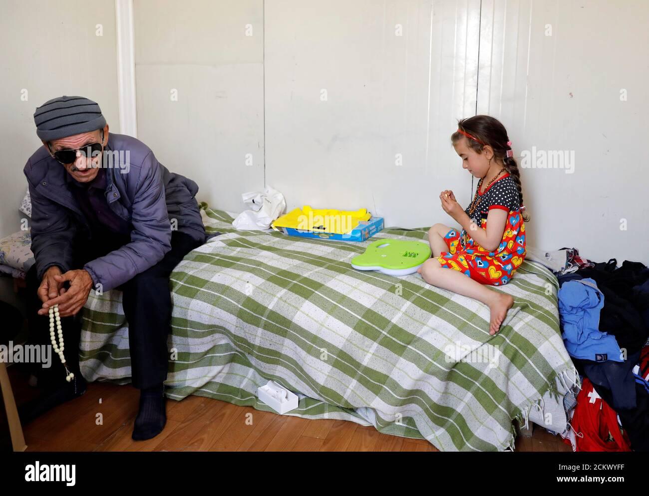 La iraquí Christina Ezzo Abada, ex rehén de militantes del Estado Islámico durante tres años, juega cerca de su padre ciego después de reunirse con su familia en una casa estrecha en un campamento de refugiados en Erbil, Irak el 10 de junio de 2017. REUTERS/Erik de Castro Foto de stock
