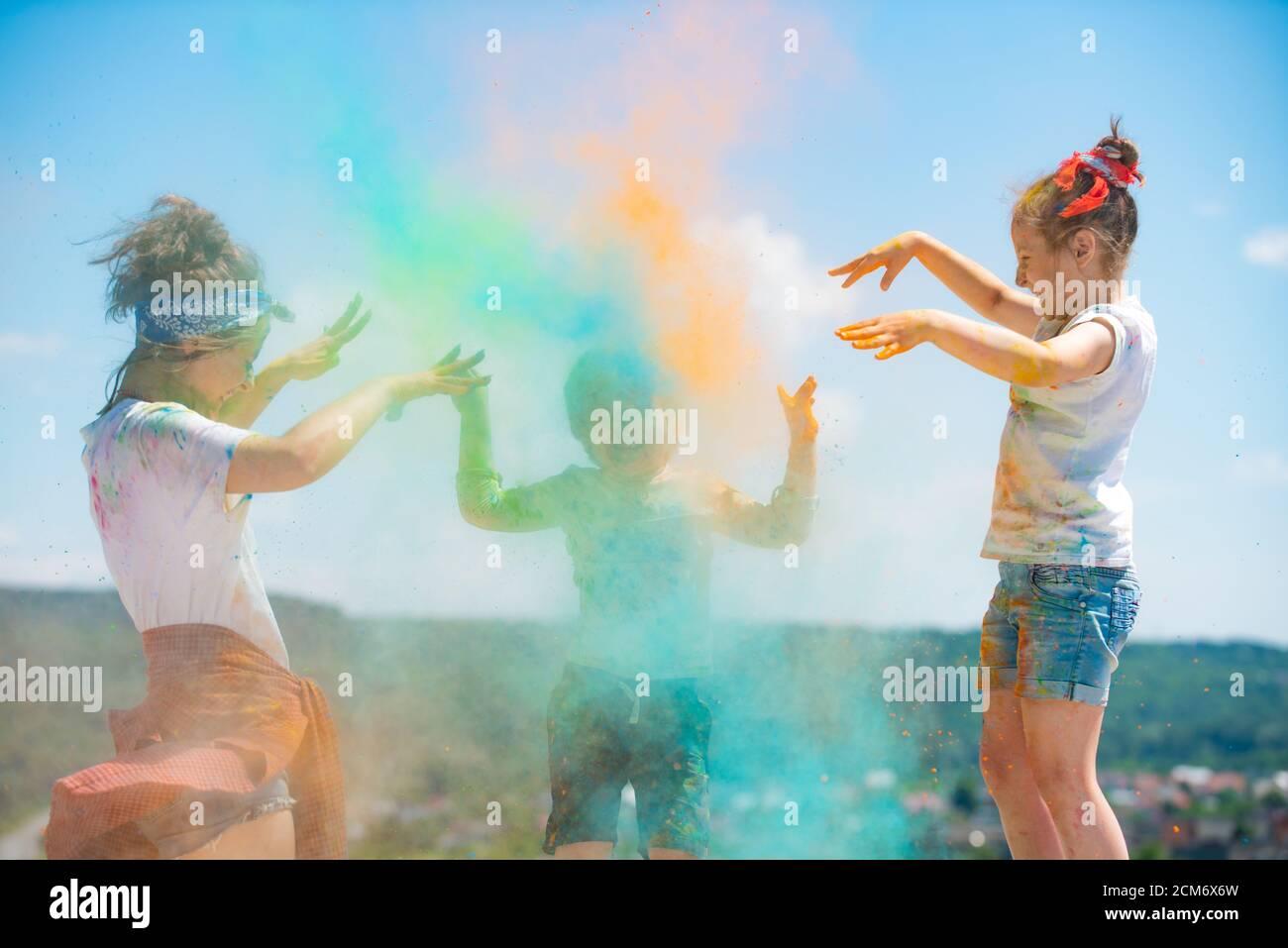 Grupo de niños disfrutando jugando con polvo de colores y salpicaduras de polvo de colores. Foto de stock