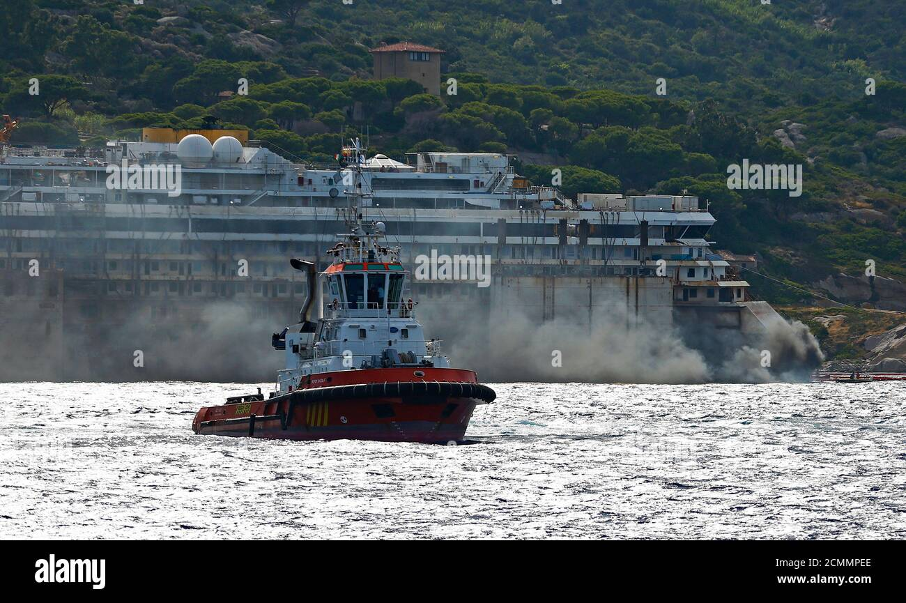 Black smoke comes out from the back of the Costa Concordia cruise liner during its refloat operation at Giglio harbour July 22, 2014. The massive hulk of the Costa Concordia is nearly ready to be towed away from the Italian island where it struck a rock and capsized two-and-a-half years ago, killing 32 people, officials said on Sunday. The 114,500-tonne Concordia has been slowly lifted from the sea floor since Monday, when salvagers began pumping air into 30 large metal boxes, or sponsons, attached around the hull. A convoy of 14 vessels will then tow the Concordia to a port near Genoa, where  Foto de stock