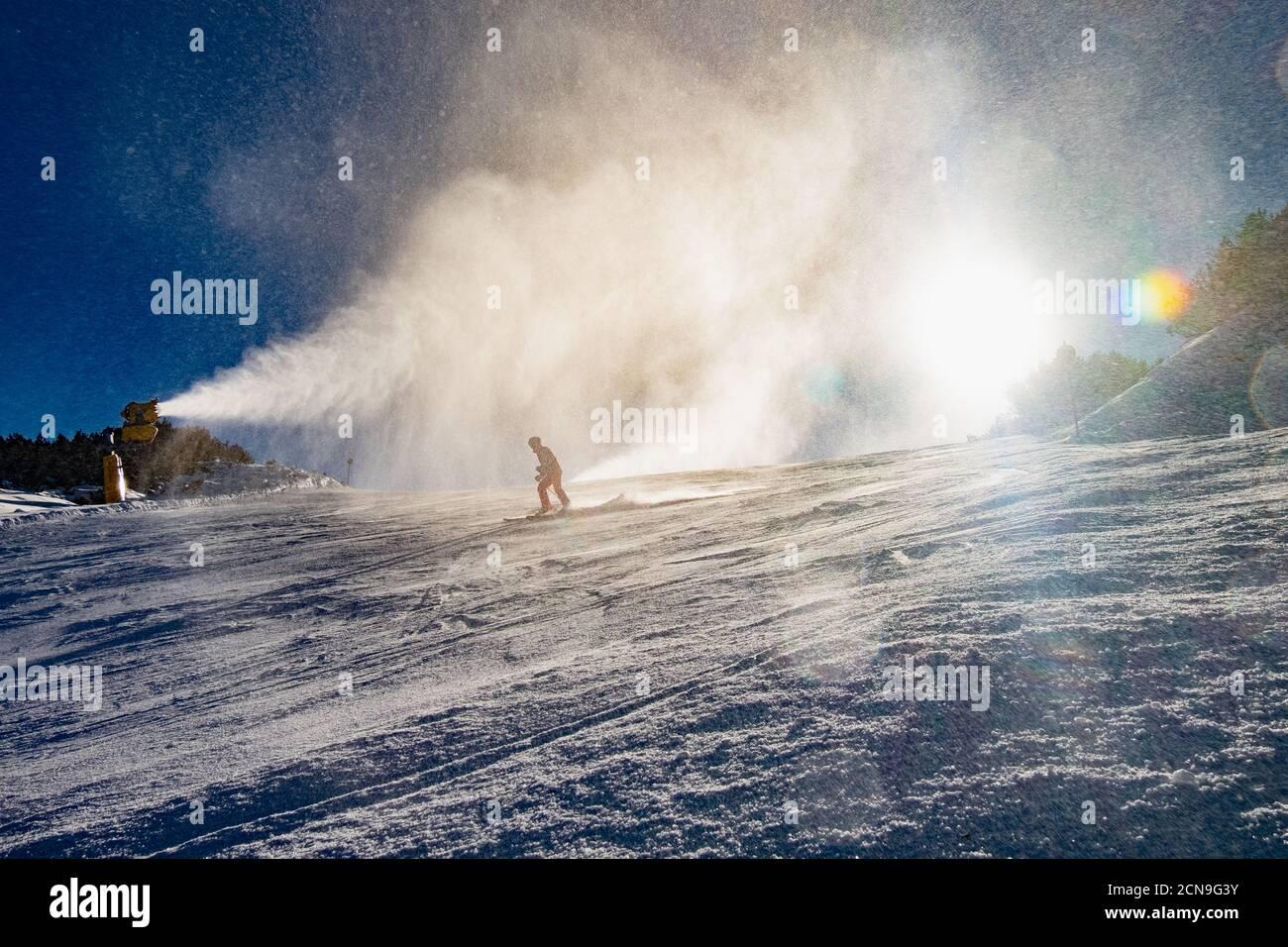 Gente esquiando abajo de canon de nieve en funcionamiento Foto de stock