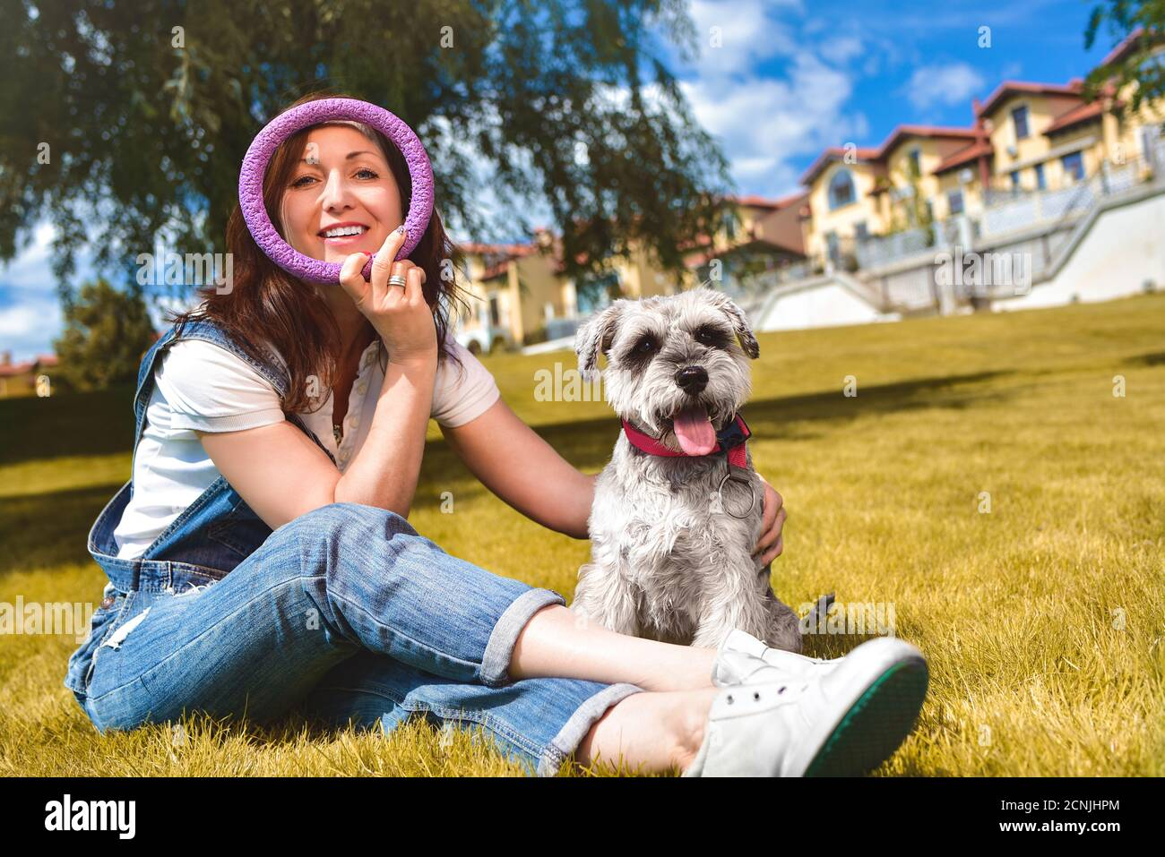 Mujer caucásica alegre jugando con su amado perro en el parque. El concepto de amor a los animales. Mejores amigos. Perro raza Schnau Foto de stock