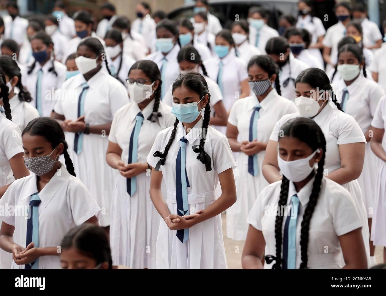 Los estudiantes que usan máscaras protectoras asisten a una meditación para la relajación mental antes del comienzo del primer día en el colegio Vidyakara, que se reabrió después de casi dos meses de bloqueo en medio de preocupaciones sobre la propagación de la enfermedad del coronavirus (COVID-19), en Colombo, Sri Lanka, 6 de julio de 2020. REUTERS/Dinuka Liyanawatte Foto de stock
