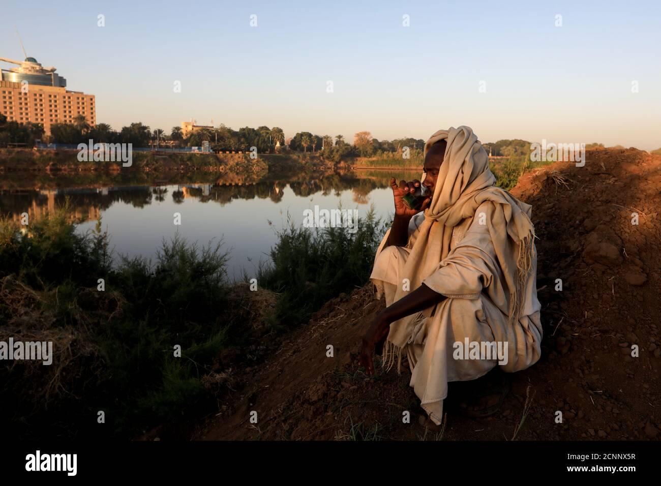 """Mohamed Ahmed al Ameen, de 55 años, un fabricante de ladrillos, bebe una taza de té mientras se sienta en el borde del Nilo Azul cerca de una fábrica al aire libre en la isla Tuti, Jartum, Sudán, 14 de febrero de 2020. """"Considero que el Nilo es algo con lo que nunca he estado, desde que nací"""", dijo Ameen. """"Yo como de ella, yo granja con ella. ¿también extrajo estos ladrillos de él? Toda mi fuente de ingresos proviene del Nilo."""" REUTERS/Zohra Bensemra BUSCA 'BENSEMRA NILE' PARA ESTA HISTORIA. BUSQUE """"IMAGEN MÁS AMPLIA"""" PARA TODAS LAS HISTORIAS. Foto de stock"""