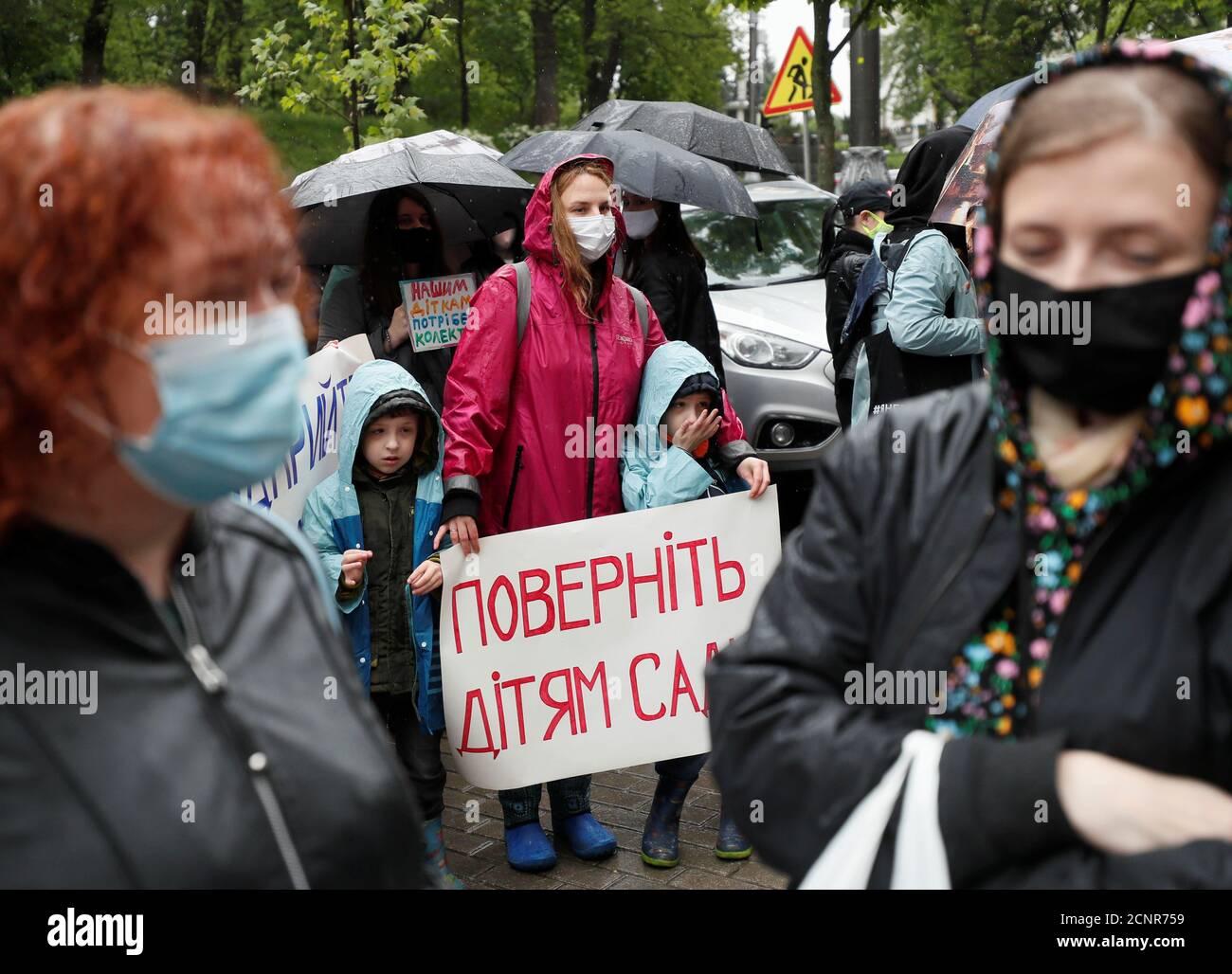 """Los manifestantes toman parte en una protesta de los padres exigiendo el alivio de las medidas de bloqueo introducidas en medio del brote de la enfermedad del coronavirus (COVID-19) y la reapertura de jardines de infancia, fuera de la sede del gabinete de ministros en Kiev, Ucrania el 19 de mayo de 2020. El cartel dice: """"Devolver a los niños a los jardines de infancia"""". REUTERS/Gleb Garanich Foto de stock"""