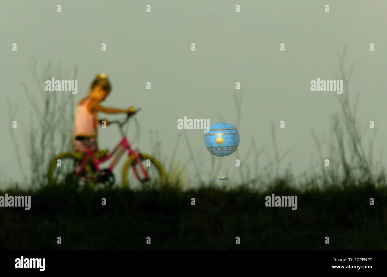 Una joven camina su bicicleta por una colina mientras un globo de helio vuela sobre el horizonte de Roma en el descanso del día 28 de julio de 2003. El globo, que se convirtió en la última atracción turística de la ciudad, ha tenido un problema bastante inusual - demasiado aire caliente. El globo solo puede volar al amanecer y al atardecer, ya que las corrientes térmicas generadas por las altas temperaturas del mediodía ponen una parada para los turistas que disfrutan de una vista aérea a la hora del almuerzo de la ciudad eterna. REUTERS/Alessandro Bianchi REUTERS DJM/WS Foto de stock