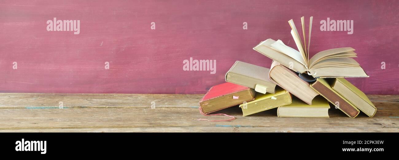 Pila de libros y libro abierto. Lectura,literatura,educación,biblioteca,concepto de oficina en el hogar, gran espacio de copia panorámica Foto de stock