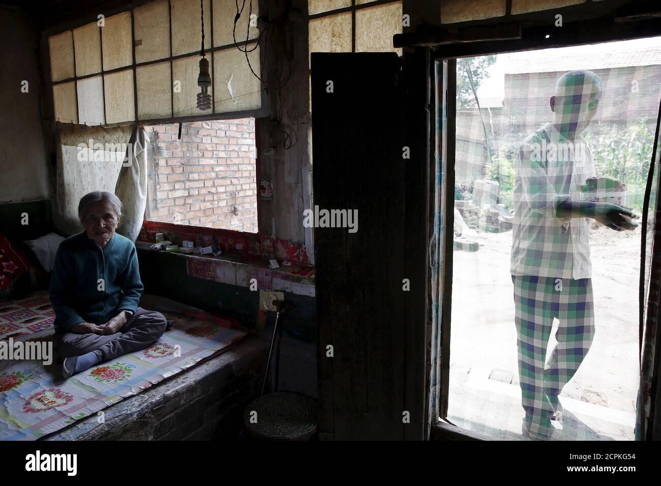 """La antigua """"mujer de la comodidad"""" China Zhang Xiantu descansa sobre una cama tradicional de ladrillo mientras su hijo trae su almuerzo en Xiyan Town, Provincia de Shanxi, China, 18 de julio de 2015. œComfort mujer? Es el eufemismo japonés para las mujeres que fueron forzadas a prostituirse y abusadas sexualmente en burdeles militares japoneses antes y durante la Segunda Guerra Mundial. Zhang es la única """"mujer de consuelo"""" sobreviviente de los 16 demandantes en Shanxi que demandó al gobierno japonés en 1995 por secuestrar a niñas y utilizarlas como """"mujeres de consuelo"""" durante la Segunda Guerra Mundial. Según información de la Comisión de Investigación de China Foto de stock"""