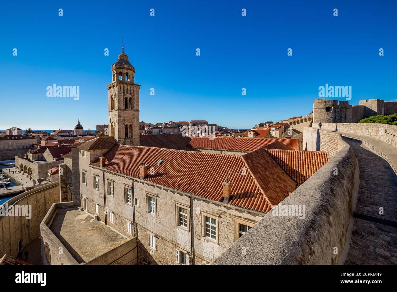 Colorido fortaleza calle escena de paseo, cielo claro día soleado. Torre de la iglesia, edificios de techos. Vista invernal de la ciudad vieja mediterránea de Dubrovnik, famoso viaje europeo y destino histórico, Croacia Foto de stock