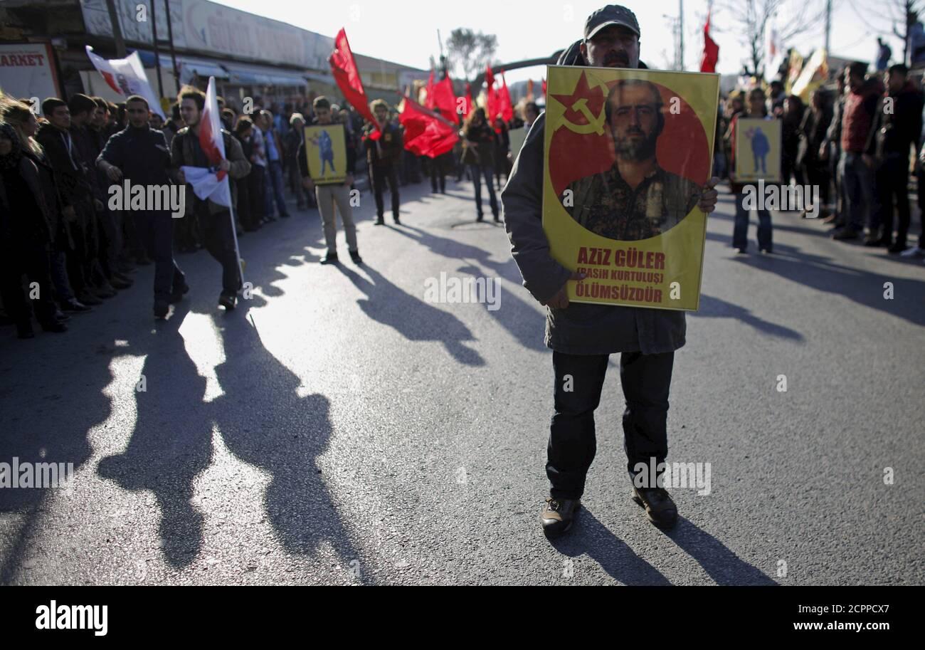 """Un hombre lleva un cartel con una imagen de Aziz Guler que dice """"Aziz Guler es inmortal"""", durante la ceremonia funeraria de Guler en el barrio Gazi de Estambul, Turquía, el 22 de noviembre de 2015. Según los medios de comunicación locales, el activista de izquierda Aziz Guler fue asesinado el 21 de septiembre en una explosión de minas terrestres mientras luchaba por la milicia YPG kurda Siria contra militantes del Estado Islámico en el norte de Siria. La familia de Guler trajo su cuerpo a Turquía el jueves, casi dos meses después de que las autoridades turcas se negaran a permitir que su cuerpo entrase en el país. REUTERS/Murad Sezer Foto de stock"""