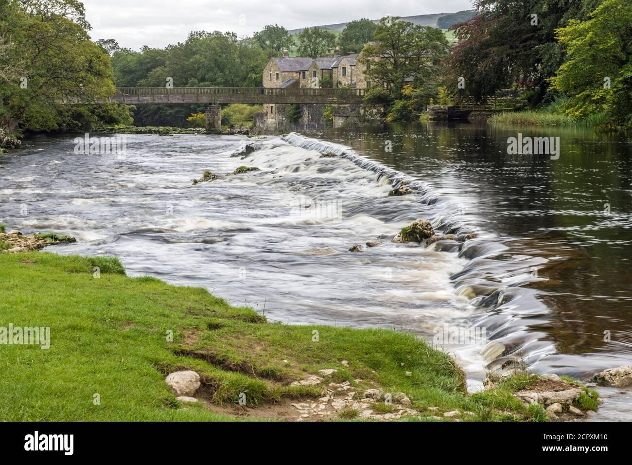 Weir en el río Wharfe sobre Linton Falls, Grassington, después de una ducha de lluvia. Hay dos llores, este es el más bajo. Wharfedale en los cuentos de Yorks Foto de stock