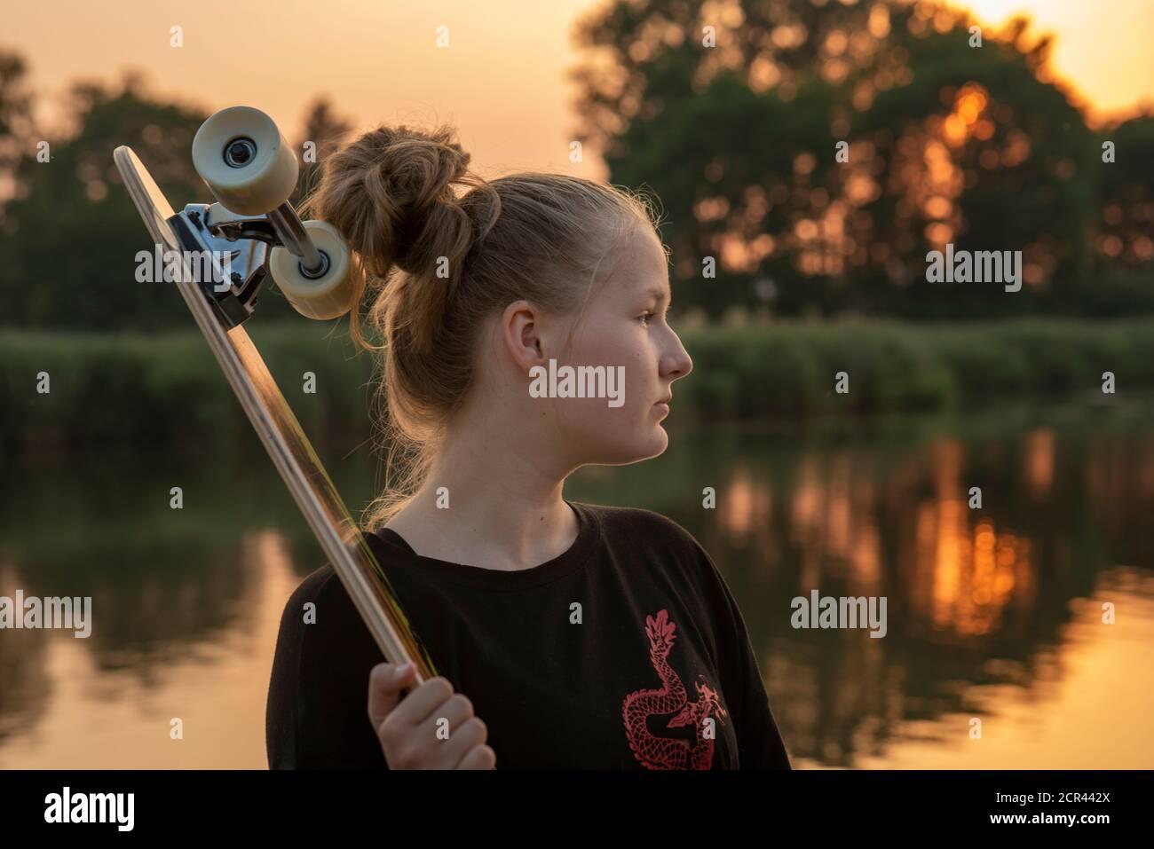 Chica está junto al lago con un longbard al atardecer Foto de stock