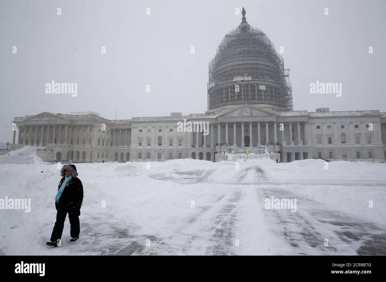Una persona camina por los terrenos cubiertos de nieve del Capitolio de los Estados Unidos en Washington el 23 de enero de 2016. El sábado, la gruesa nieve cubrió el área de Washington, D.C. como una carretera paralizada, ferrocarril y aerolínea potencialmente sin precedentes en la costa este de Estados Unidos, desde Carolina del Norte hasta Nueva York. REUTERS/Jonathan Ernst Foto de stock