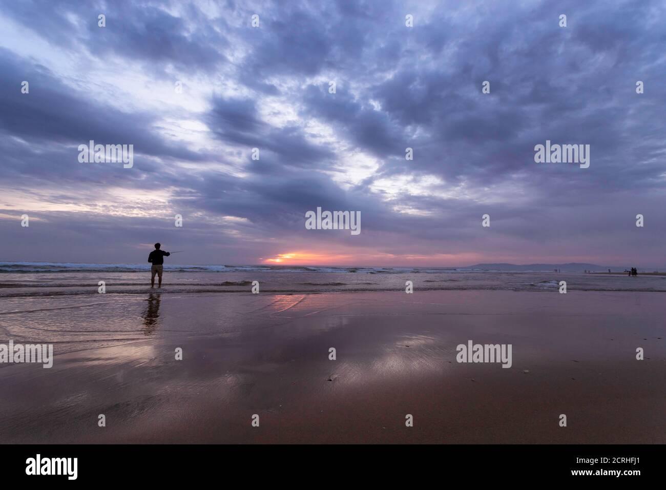 Un joven pescando en el mar abierto a lo largo de la costa del Océano Atlántico en Costa da Caparica en Lisboa, Portugal. Un chico atractivo que sostiene la pesca ro Foto de stock