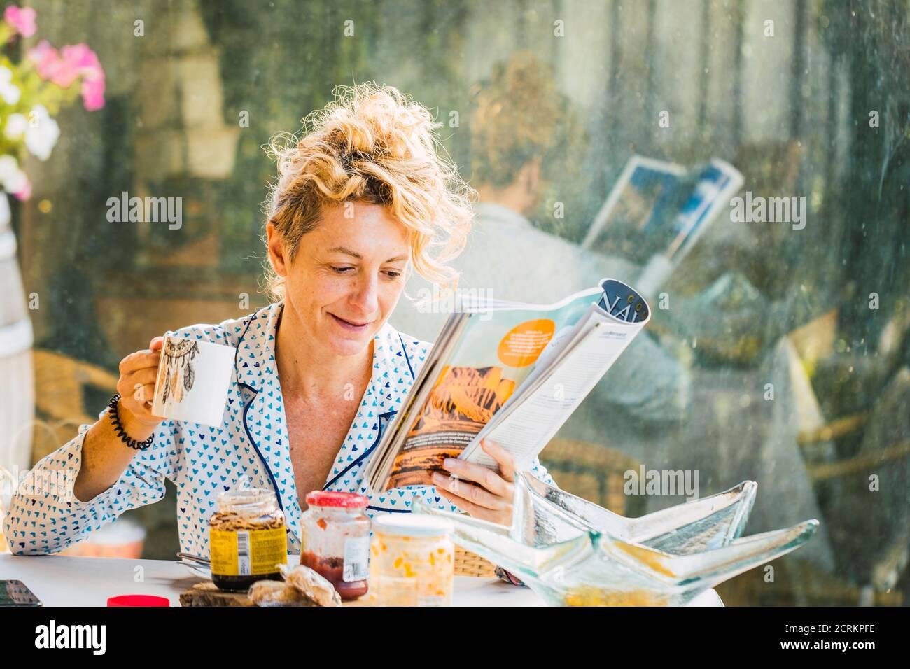 Rubia joven madura en pijamas en casa durante el desayuno, leyendo una revista y tomando una taza de café Foto de stock