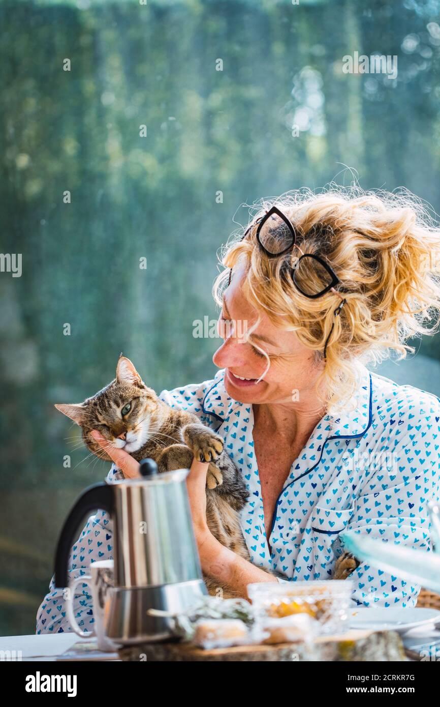 Rubia joven madura con gafas en pijama en casa en el desayuno, leyendo una revista y teniendo un momento con su gato. Foto de stock