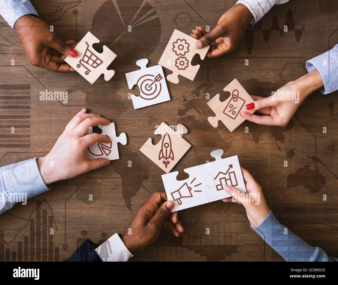 Collage creativo con gente de negocios sosteniendo piezas de rompecabezas con marketing Iconos de estrategia Foto de stock