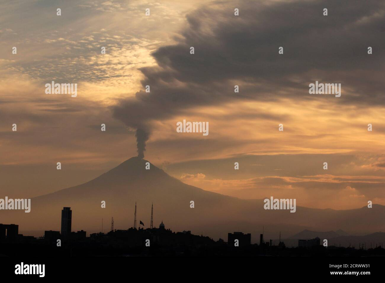 The Popocatepetl volcano spews a cloud of ash and steam high into the air in Puebla May 11, 2012.  Mexico last month raised the alert level for the volcano Popocatepetl, 50 miles (80 km) southeast of Mexico City, after it began pumping out red-hot fragments of rock and ash. The country has been closely monitoring the 17,900-foot (5,450-metre) volcano, which has prompted school classes in nearby villages to be suspended on days of higher activity. REUTERS/Imelda Medina (MEXICO - Tags: ENVIRONMENT) Foto de stock