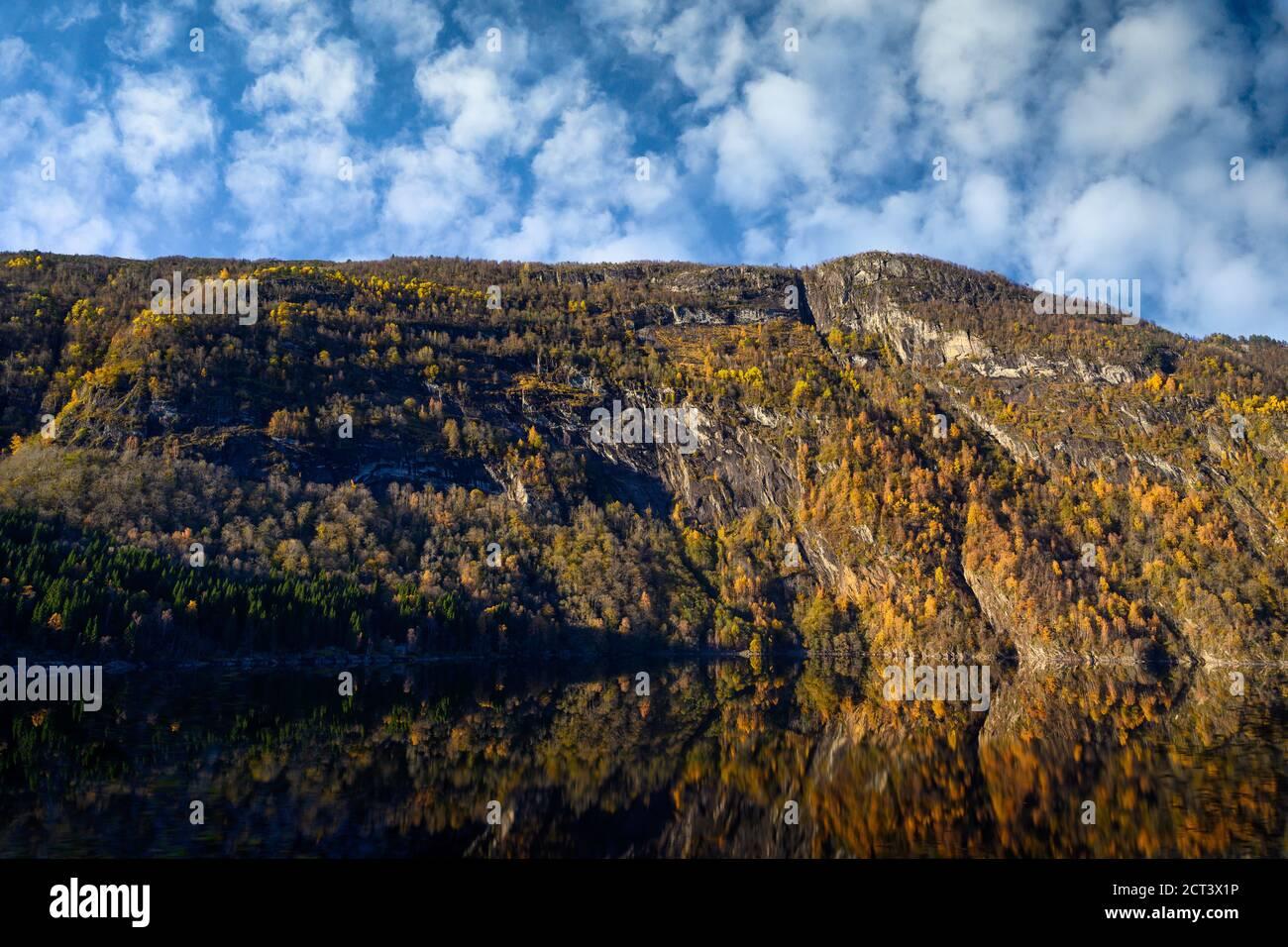 Las montañas en otoño cambian el color de las hojas para cambiar a reflejos amarillos y naranjas en el agua. Es una hermosa vista natural de Noruega. Foto de stock