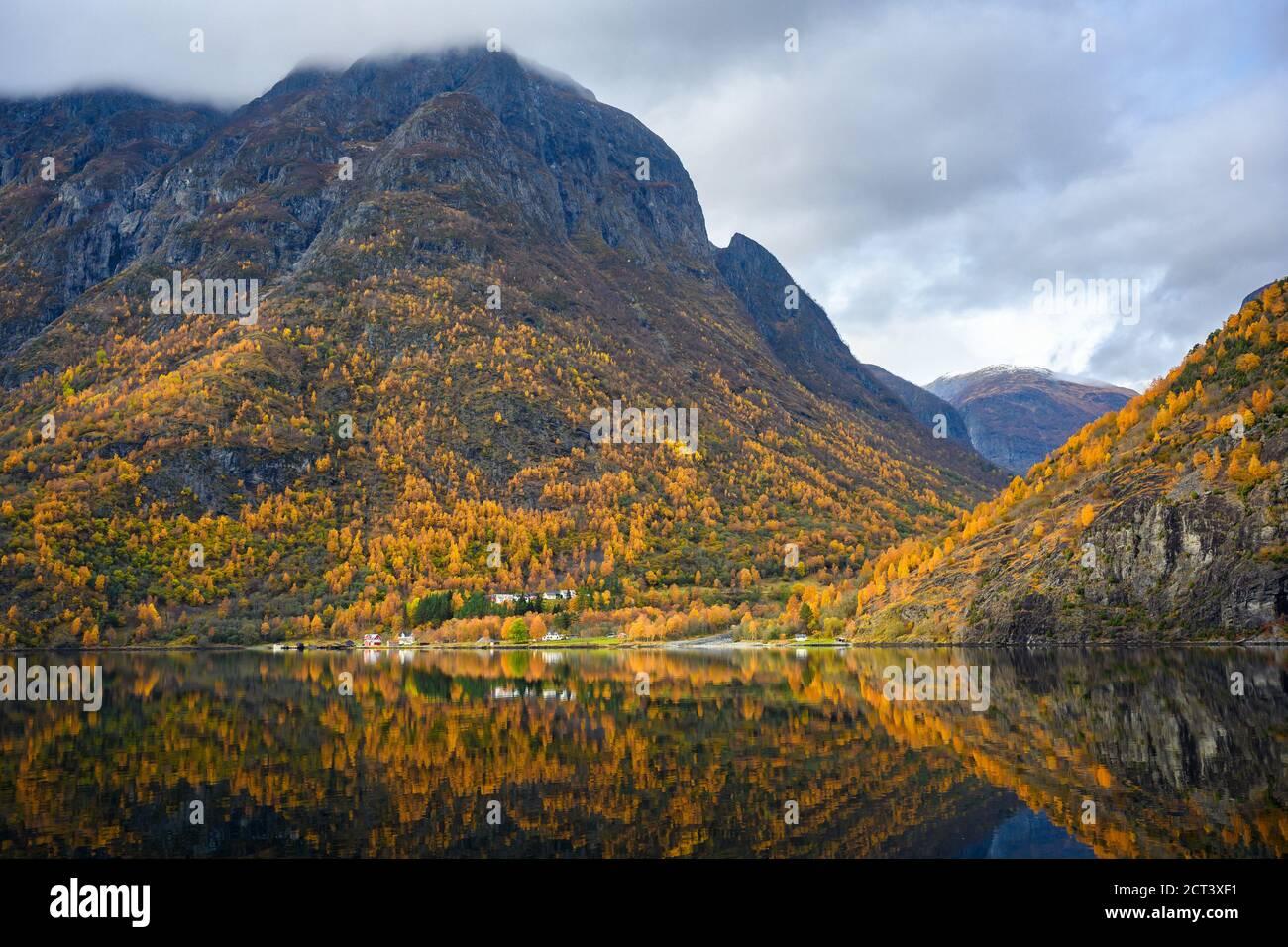 Pequeño pueblo en la costa y las montañas en la temporada de otoño que reflejan el agua. Contemple desde un viaje en barco la belleza de Sognefjord Crui Foto de stock