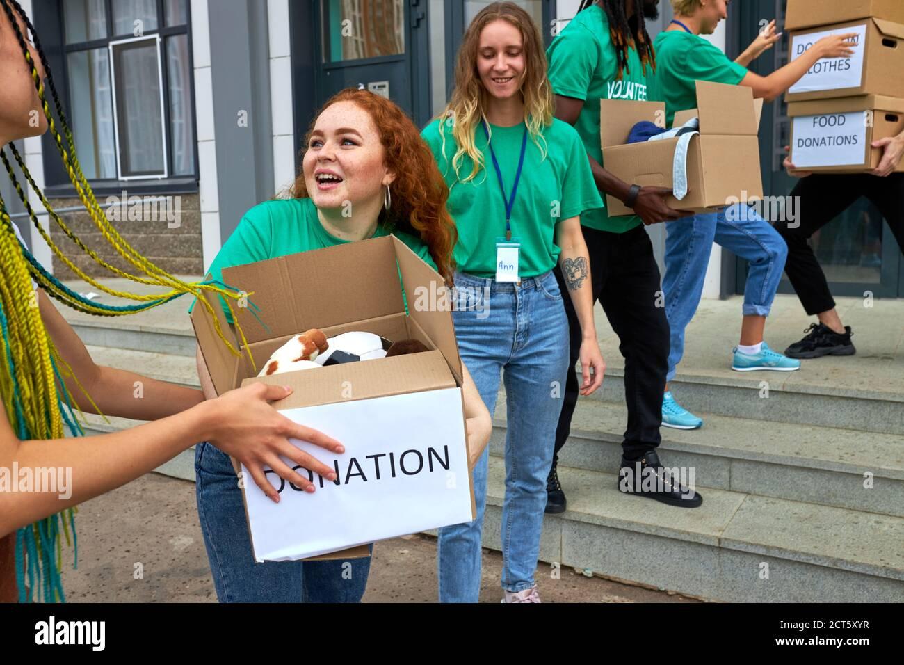 diversos voluntarios empaquetando, recogiendo ayuda humanitaria en caja de donaciones. grupo multiétnico de personas que trabajan en fundaciones caritativas ayudando en cris Foto de stock