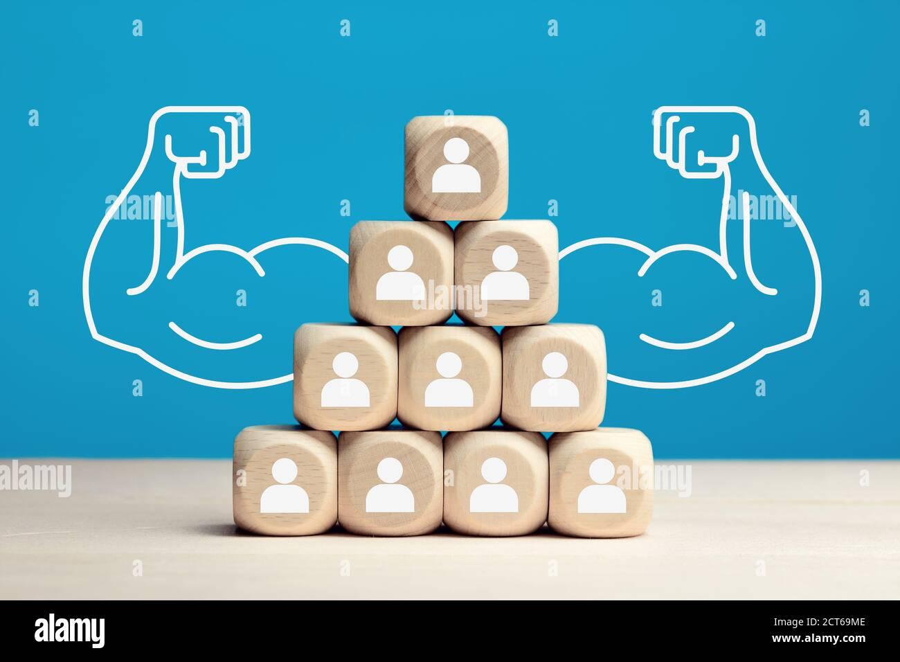Bloques de madera apilados como pirámide de jerarquía con iconos de personas. Poder de trabajo en equipo, solidaridad o cooperación en concepto empresarial. Foto de stock