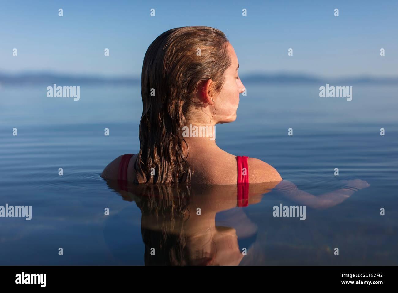 Una adolescente nadando en un lago, cabeza y hombros sobre el agua del lago al amanecer, los ojos cerrados Foto de stock