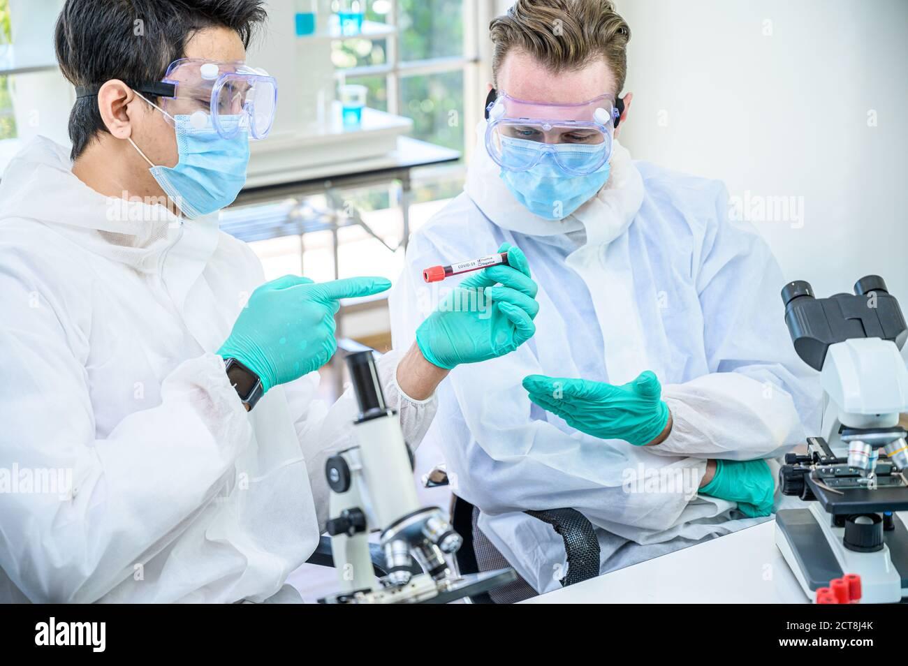 Un hombre de la pareja de científicos usando traje de protección que sostiene la vacuna contra el Coronavirus y trabajando con muchos equipos de laboratorio para la investigación de la vacuna en el laboratorio. Viru Foto de stock