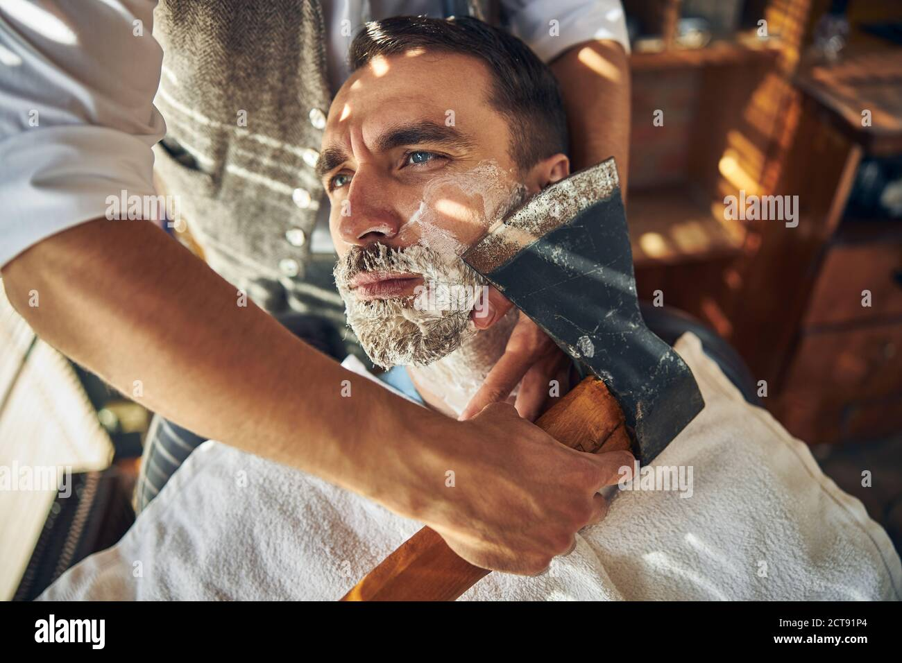 Un hombre joven guapo que está siendo afeitado con un hacha Foto de stock
