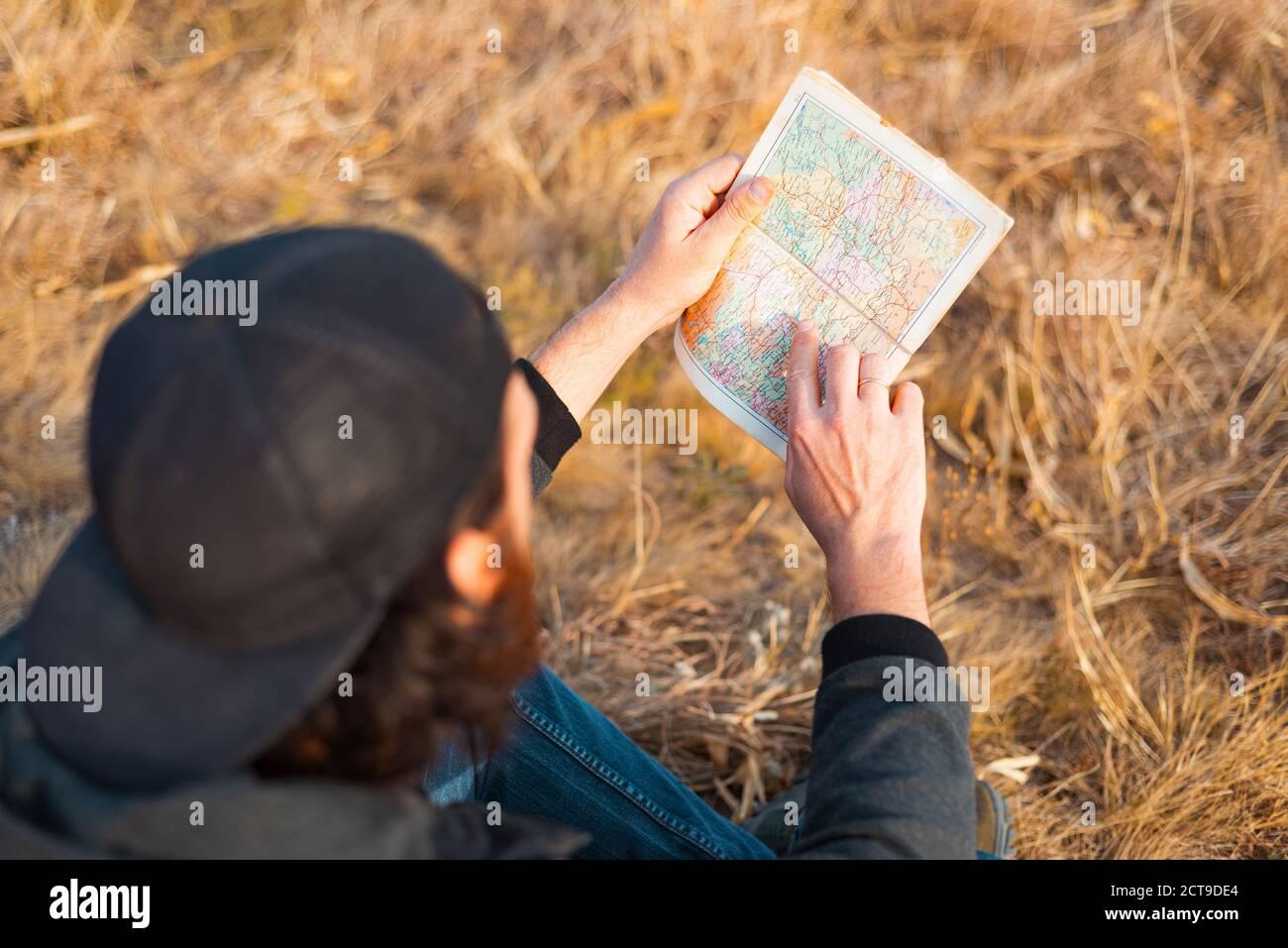 Un joven está sentado en el campo y mirando en un mapa . Foto de stock