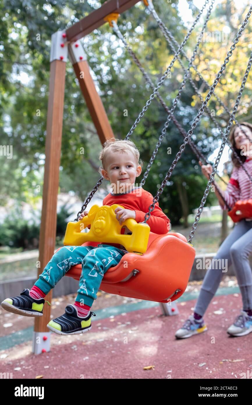 Madre con hijo Diversión Swinging Together at Playground Foto de stock