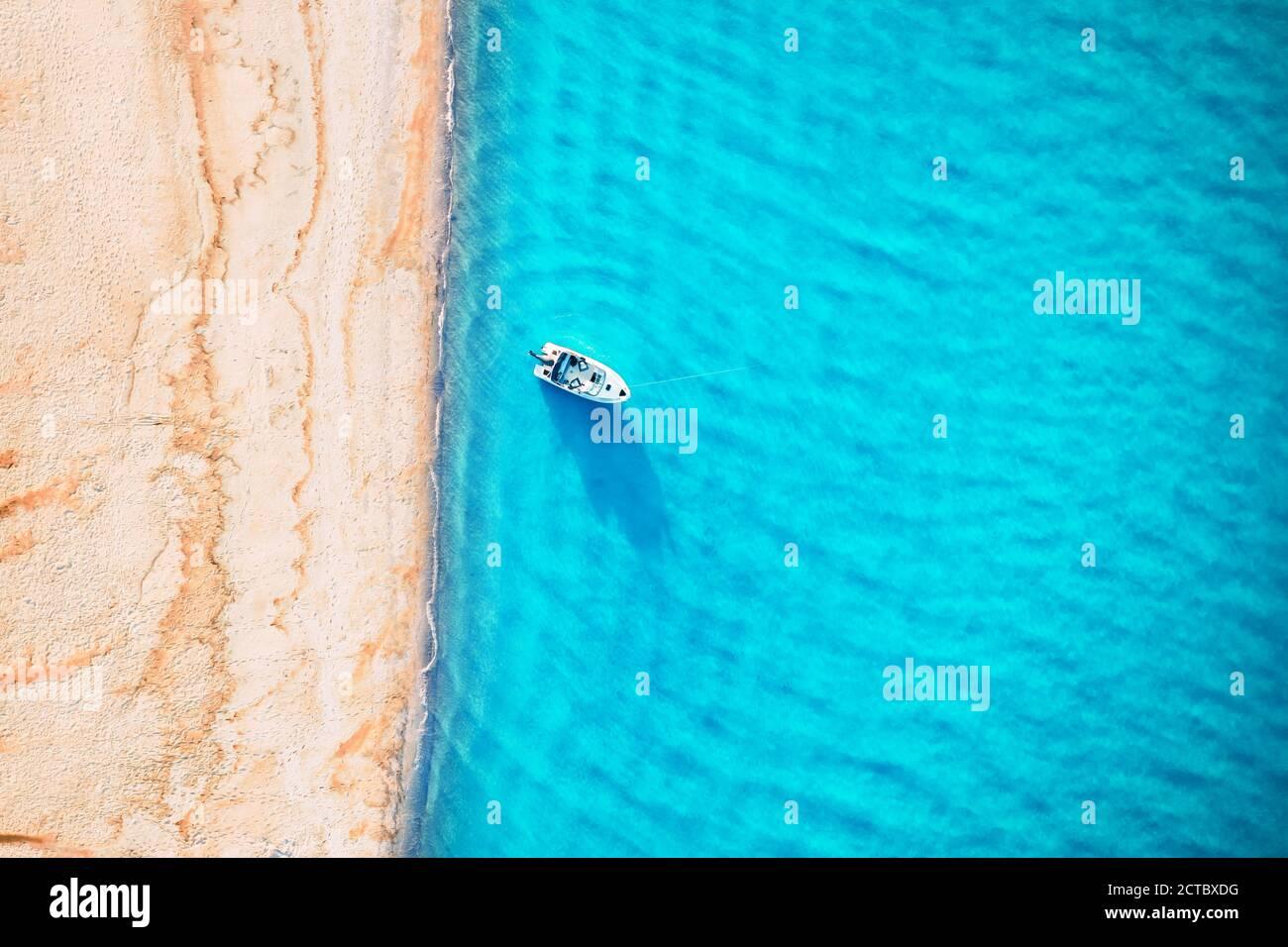 Yate blanco y olas de agua turquesa desde la vista superior. Playa con arena amarilla resplandeciente por la luz del sol. Viajes vacaciones de verano paisaje marino fondo de drone Foto de stock