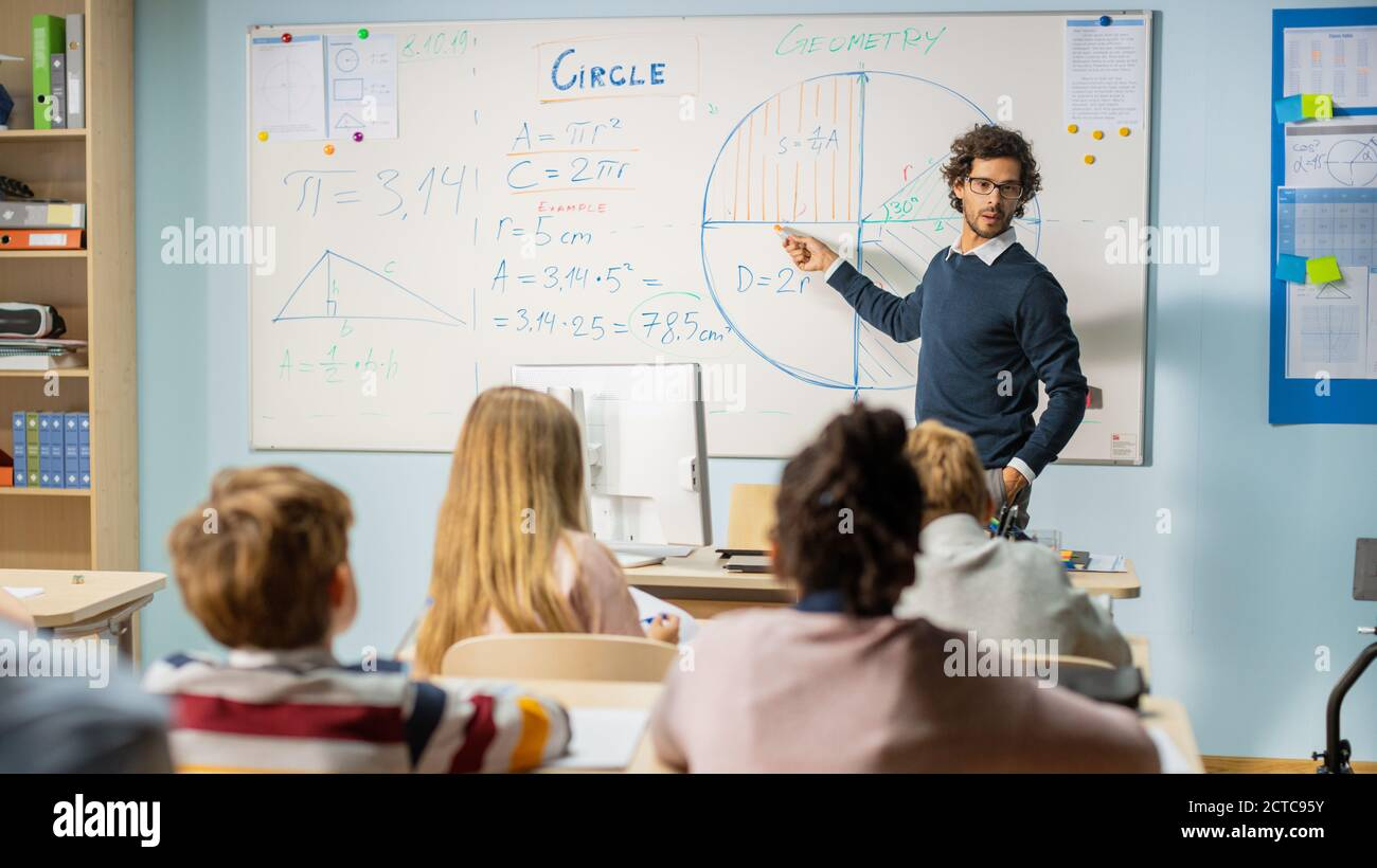 Tiro de Maestro explicando la lección al Aula llena de niños brillantes diversos, en la Escuela Primaria Grupo de niños multiétnicos inteligentes de Aprendizaje de Ciencia Foto de stock