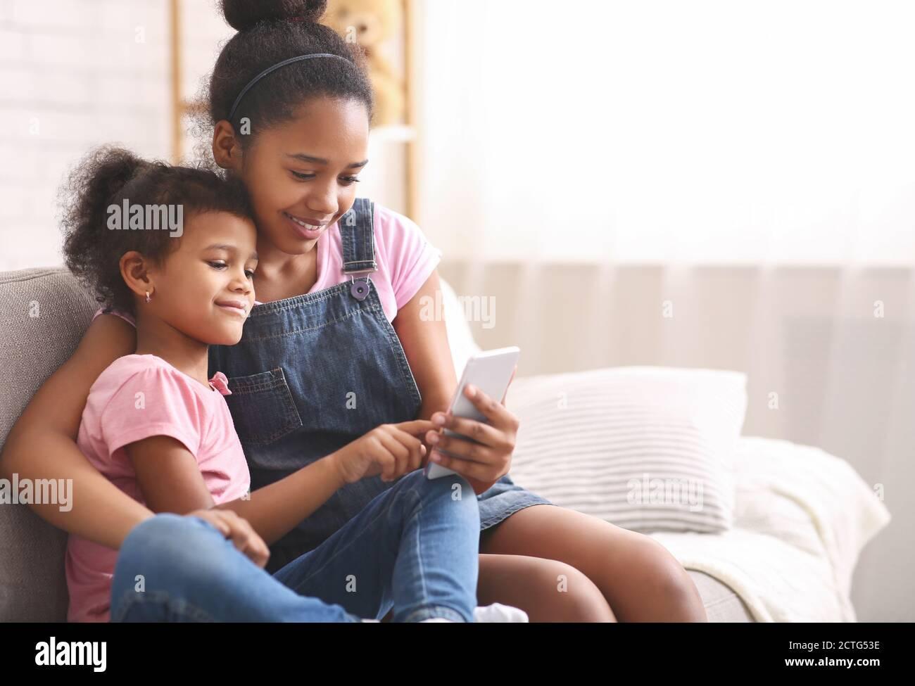 Niña afroamericana jugando en el celular de su hermana Foto de stock