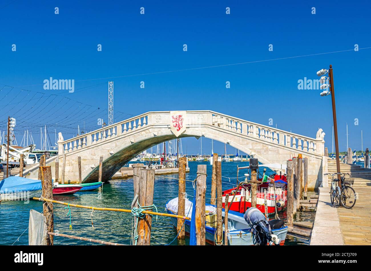 Puente de piedra Ponte di Vigo a través del canal de agua vena con coloridos barcos cerca del terraplén del muelle en el centro histórico de la ciudad de Chioggia, cielo azul de fondo en el día de verano, Región Veneto, Norte de Italia Foto de stock