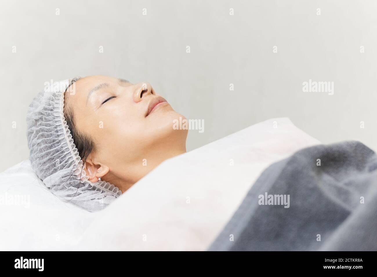 Hermosa mujer con la piel sana limpia relajante tumbado en el salón de spa. Foto de stock