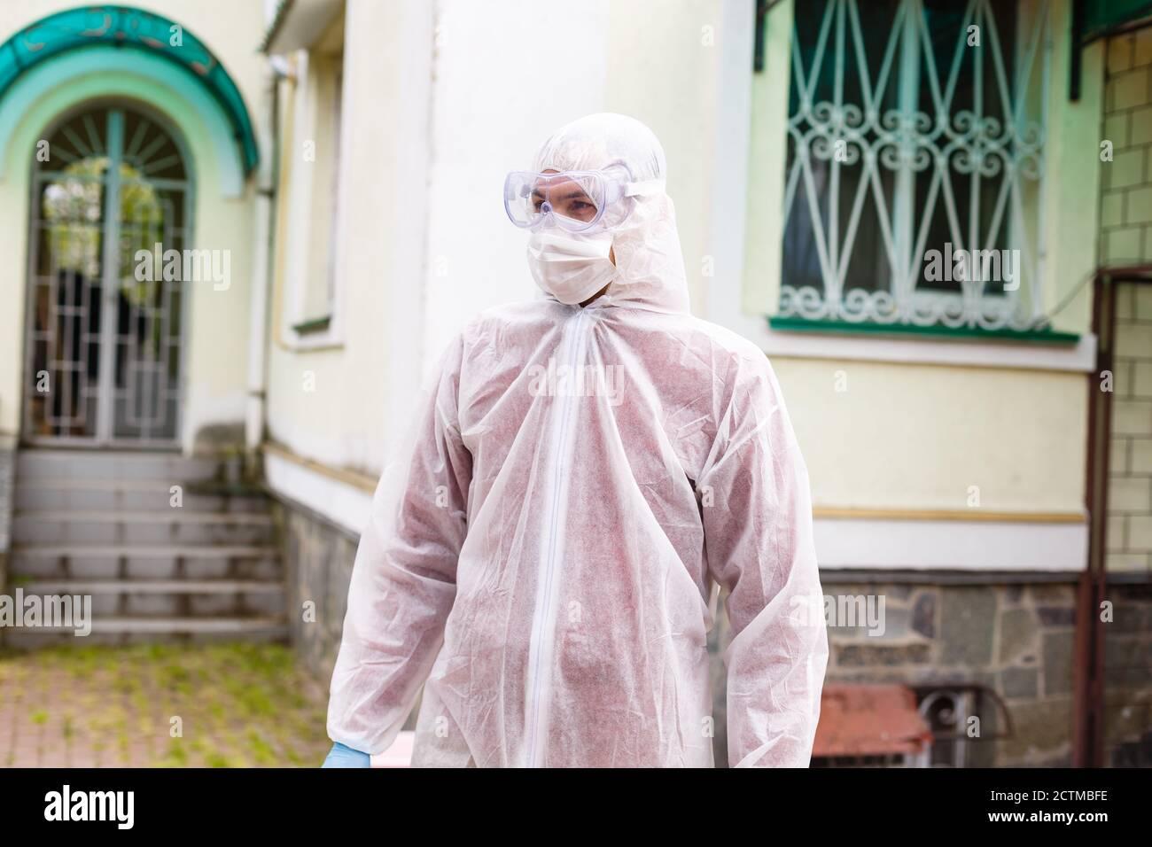 El enfoque selectivo de hombres sonrientes científico en máscara protectora y palo mirando a la cámara en el exterior Foto de stock